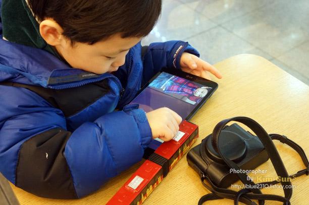 G Pad 8.3과 카메라를 연결해 하루동안 찍은 사진을 아이에게 보여주고 있다.