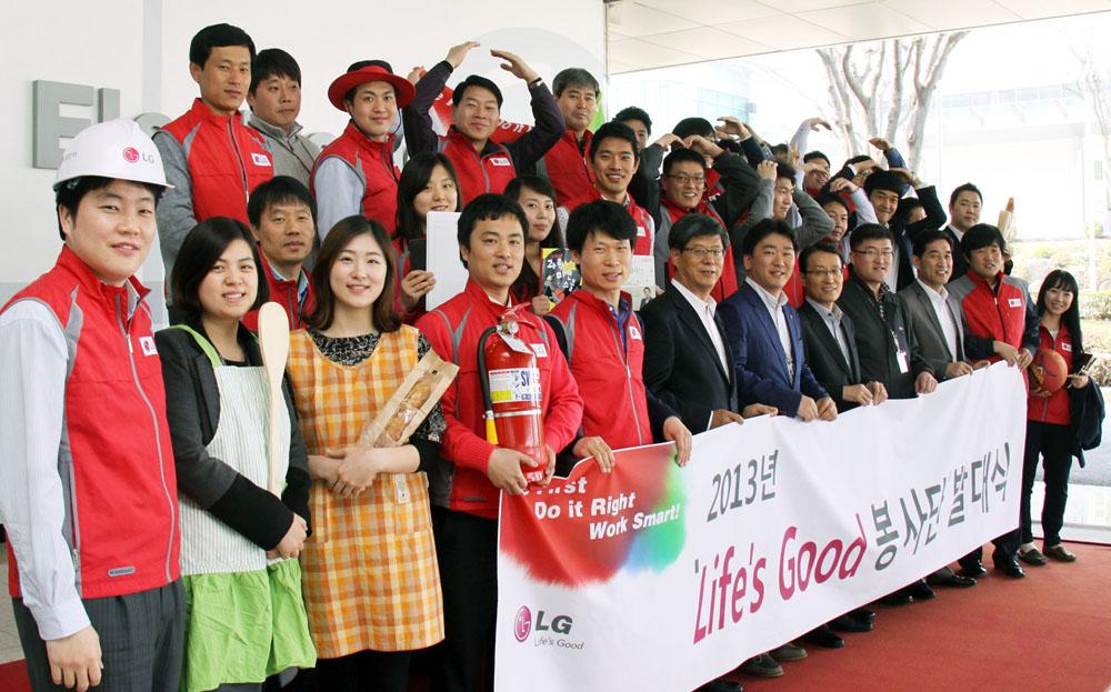 2013년 Life's Good 봉사단 발대식 단체 사진으로 앞줄의 사람들이 봉사단 발대식 현수막을 들고 있고 다수의 사람들이 빨간 상의를 입고 있다.