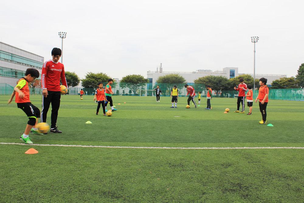 봉사단원들이 잔디축구장에서 아이들에게 축구를 가르쳐주고 있는 모습이다. 삼삼오오 짝을 이뤄 공을 가지고 연습하고 있다.