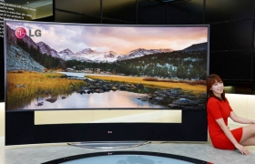 모델이 LG전자와 LG디스플레이가 세계 최초로 개발한 '105형 곡면 울트라HD TV' 앞에서 포즈를 취하고 있다.