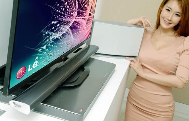 사진에서 TV아래 놓여있는 제품이 사운드 플레이트(LAB540W), TV 스탠드 위에 놓여 있는 제품이 사운드 바(NB5540), 모델이 손을 얹고 있는 제품이무선오디오(NP8740)다.
