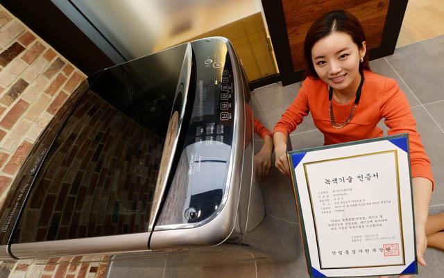 서울 여의도 소재 LG트윈타워에서 여성 모델이 LG 세탁기의 '터보샷' 기술로 받은 '녹색기술' 인증서를 소개하고 있다. 제품은 이 기술을 적용한 LG '블랙라벨' 세탁기다.