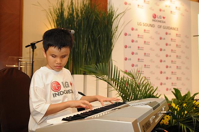 청중과 기자들 앞에서 시각 장애 학생이 피아노 연주를 하고 있다.