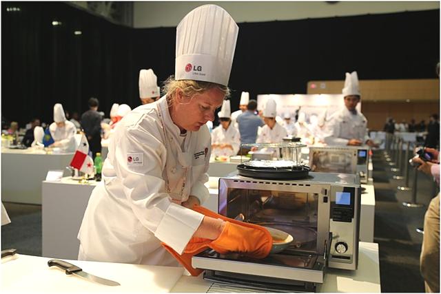 하얀 조리복과 모자를 쓴 외국인 참가자가 광파오븐을 이용해서 요리중이다