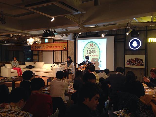 나눔데이 행사중 진행되고 있는 공연 장면. 무대 위에서 혼성 그룹 달과 바둑이가 클래식 기타를 치며 노래 부르고 있고 무대 앞에는 참석자들이 앉아 노래를 듣고 있다.