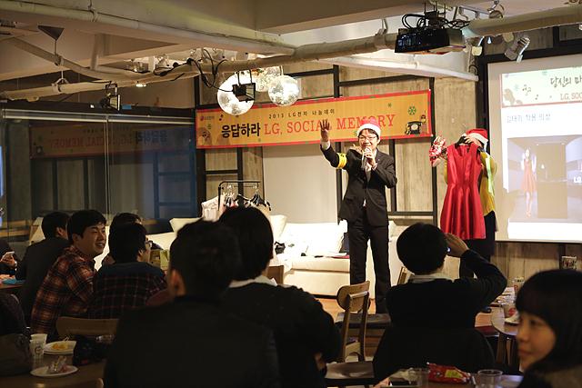 나눔경매가 진행되고 있는 장면. 스태프 한 명이 빨간색 드레스와 구두를 들고 무대 위에 서 있고 그 옆에 사회자가 경매 참여자들을 바라보며 손짓하고 있다.