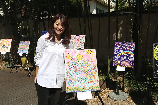카페 전시장에서 이소영 사원이 전시된 그림과 사진을 찍고 있다.