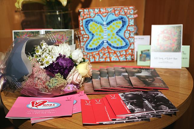 탁자 위에 나비 그림과 꽃다발, 여러 개의 책자가 올려져 있다.