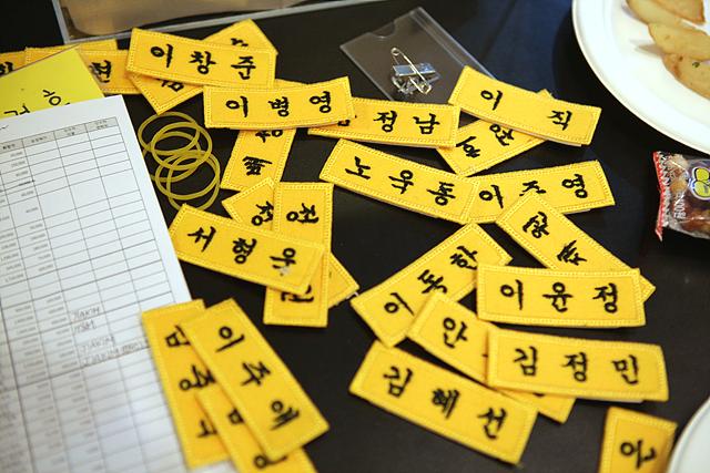 노란색 천 이름표에 검정색 실로 이름이 자수로 새겨져 있고, 여러 개의 이름표들이 테이블 위에 어지럽게 놓여 있다.