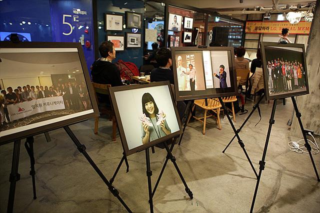 소셜LG 나눔데이 행사장 내부의 모습으로, 4개의 이젤 위에 크게 인쇄된 2013년 LG전자 행사 사진이 액자에 끼워져 놓여 있다.