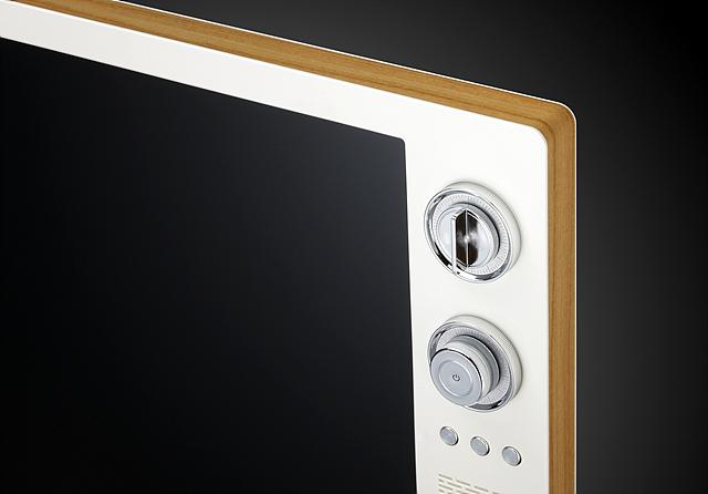 LG 클래식 TV의 측면으로 테두리는 우드 타일로 둘러져 있고 TV의 오른쪽 상단에 음량 조절 스크롤과 전원 버튼이 있다.