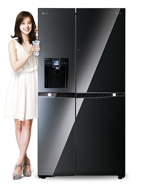 블랙 색상의 정수기 냉장고 앞에 하얀 원피스를 입은 김태희가 물 컵을 들고 서 있다.