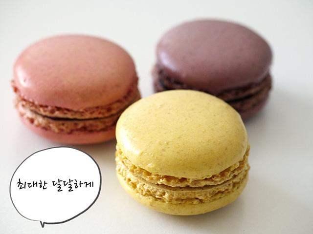 """달콤해 보이는 삼색의 마카롱이 올려져 있고 """"최대한 달달하게"""" 라는 말풍선이 달려있다."""