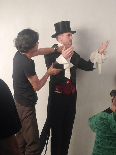 외국 모델이 턱시도를 입고 촬영을 준비하고 있다. 그 옆에서 감독이 모델의 각도를 직접 수정해주고 있다.