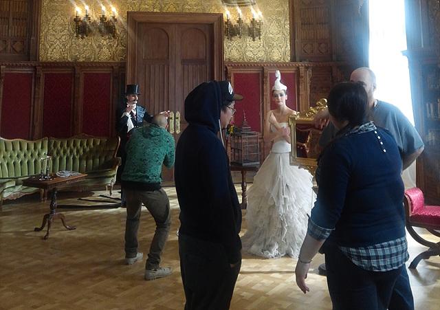흰 드레스를 입은 모델과 턱시도를 입은 모델이 촬영을 준비하고 있으며 그 앞으로 스태프들이 대화를 나누고 있다.