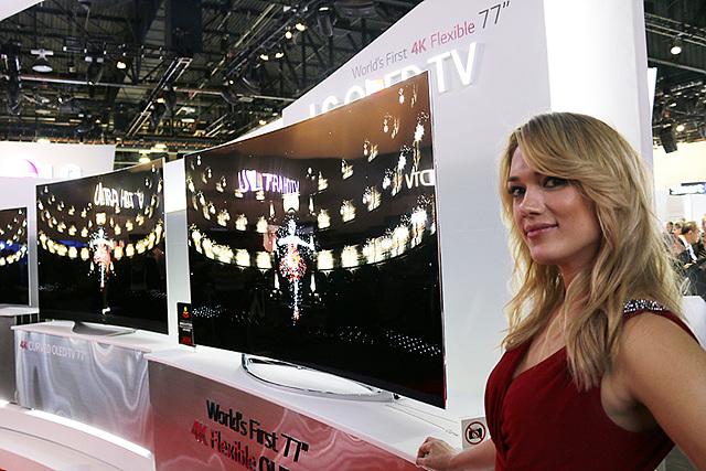 금발의 여자 모델이 가변형 UHD 올레드 TV 앞에 서있다. 옆으로 곡선으로 휘어진 TV두 대가 나란히 놓여있다.