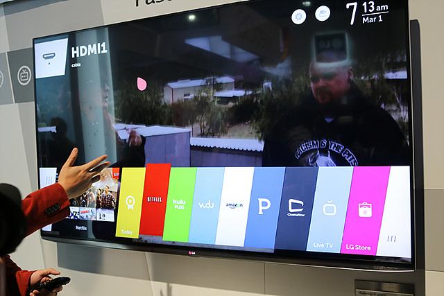 한 사람이 손으로 웹OS 스마트 TV를 가리키고 있다. 스마트 TV가 사진 중앙에 있고, 여러가지 기능들이 시연 중이다.