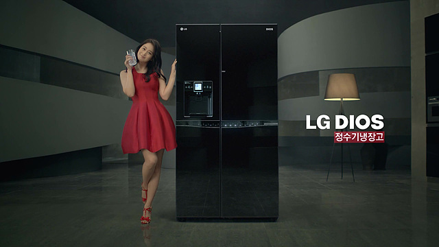 정수기 냉장고 옆에 빨간 원피스를 입은 김태희가 포즈를 취하고 있다.