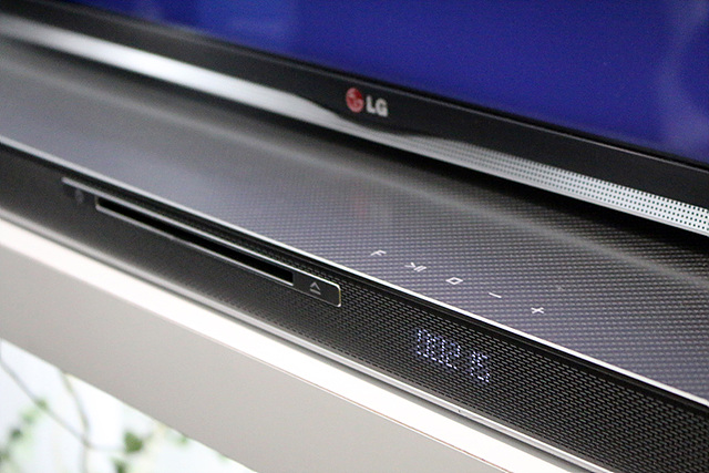 TV아래에 사운드 플레이트가 놓여있다. 검정색 사운드 플레이트로 앞 모습이 찍혀있다.