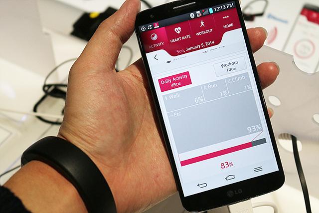 팔목에 라이프밴드 터치를 차고 휴대폰을 들고 있는 모습이다. 라이프밴드 터치와 연결하여 실시간으로 심박수를 체크하고 있다.