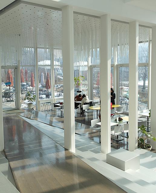 헤이리 예술마을에 있는 현대미술관 내부 모습으로 하얀색 기둥들과 넓은 창이 보이며 테이블 앞에 사람들이 앉아 있다.