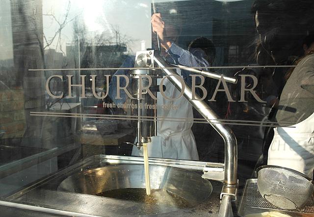 츄러스 가게인 츄로바에서 츄러스를 뽑아내는 모습을 유리창 밖에서 촬영한 사진