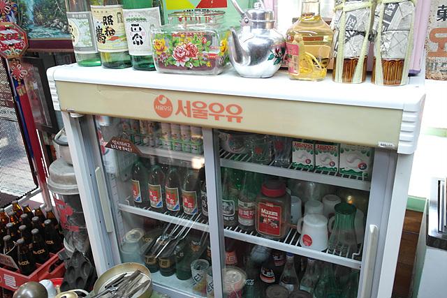 한국 근현대사 박물관에 전시되어 있는 옛날 우유냉장고. 냉장고 안쪽에 옛날 우유와 술병이 들어 있고 우유냉장고 위에 양은주전자 등 옛날 소품들이 놓여 있다.