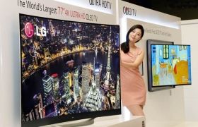 모델이 (왼쪽)77인치 곡면 올레드TV와 (오른쪽)갤러리 올레드 TV 사이에서 포즈를 취하고 있다.