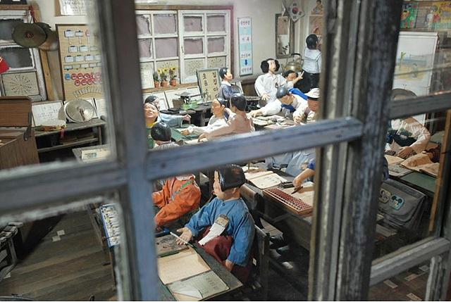 낡은 창문 너머로 옛날 교실 풍경이 보임. 개량한복을 입은 학생, 커다란 털 귀마개를 한 학생 인형들이 책상 앞에 앉아 있다.