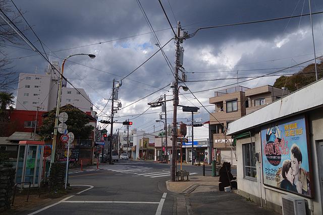 오우메 역근처의 모습으로 하늘 위엔 구름이 가득 떠있고 우측에는 손간판도 보인다.