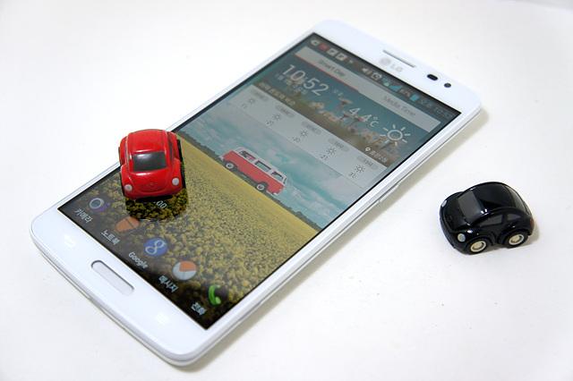 GX의 전용앱을 켜놓은 위로 빨간 자동차 미니어쳐가 한 대 올려져 있고 GX의 옆에 검은 자동차 미니어쳐가 세워져 있다.