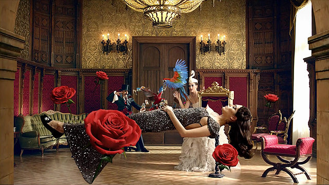 흰 드레스를 입을 모델 앞으로 다른 모델이 공중에 떠서 누워 있고 그 주위로 장미꽃이 같이 떠 있는 모습이다.