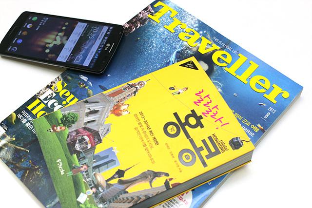 Traveller라는 잡지 위로 랄랄라! 홍콩이라는 책이 올려져 있고 그 옆으로 블랙 색상의 G2가 비스듬하게 놓여 있다.