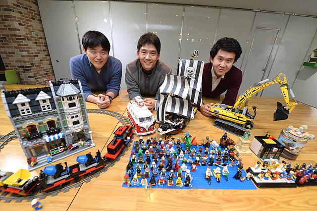 테이블 위에 3명의 참석자가 자신이 좋아하는 레고를 올려 놓고 포즈를 취하고 있다.