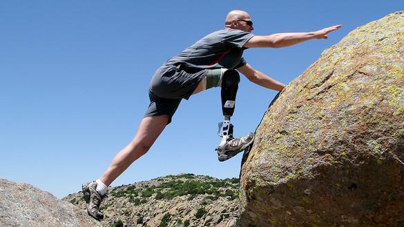 한 남성이 오른발에 로봇의족을 착용한 채 바위에서 다른 바위로 올라가고 있다. 의쪽을 착용한 발로 옮겨가는 바위를 딛고 있다.