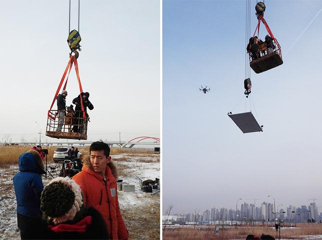 스태프들이 고공촬영을 준비하기 위해 크레인 안에 들어간 모습과 하늘 높이 올라간 모습이다.