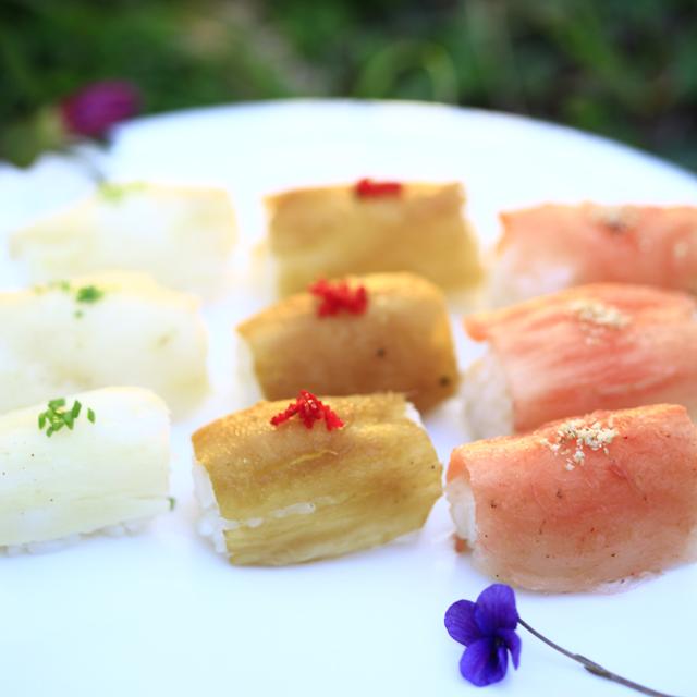 세 가지 다른 재료와 색을 가진 초밥이 흰 접시 위에 올려져 있다.