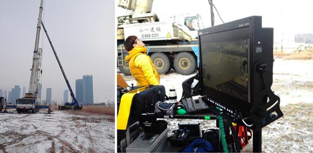 촬영을 위해 크레인과 트럭이 준비되어 있고 옆엔 모니터와 스태프가 서있는 모습이다.