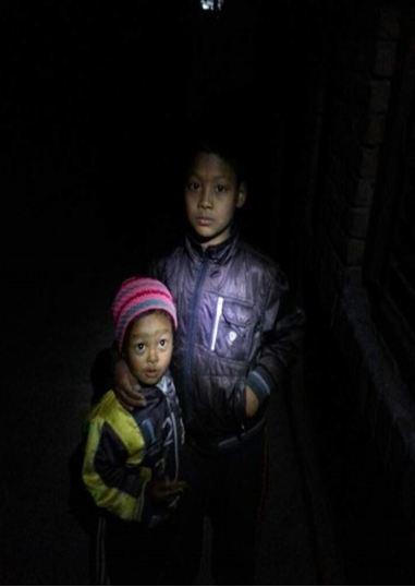 어두운 밤 골목에서 찍은 네팔 남매의 사진. 남매의 얼굴에 손전등을 비춰 찍은 사진이다.