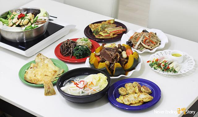하얀 식탁위에 호박 갈비찜과 삼색 나물, 잡채, 전 등의 명절 음식이 한상 차려져 있다.