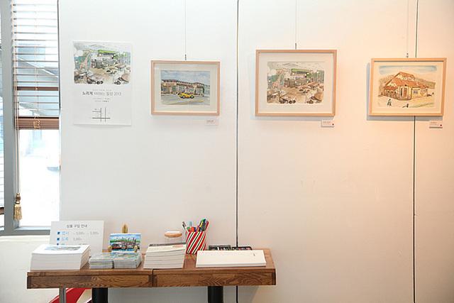 셀프전시회 현장, 하얀 벽에 걸린 액자에 직접 그린 그림들이 전시되어 있으며 아래 책상에 도록과 팜플렛 등이 놓여져 있다