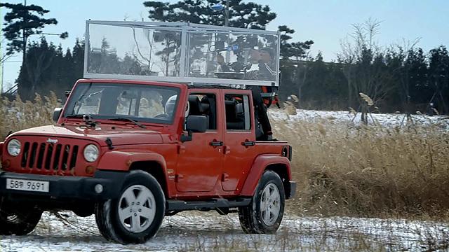 빨간 지프차 위에 투명한 박스를 설치해놓고 그 안에 로보킹을 넣어 놓은 모습이다.