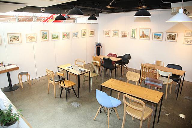 샐프 전시회를 열 수 있는 갤러리 내부전경, 하얀 벽에 다양한 작품들이 걸린 액자가 걸려있고 가운데 책상과 의자들이 놓여져 있다