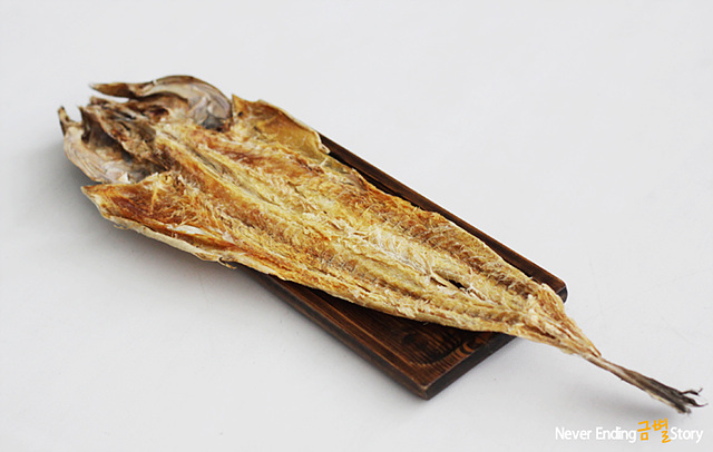 조그만 나무 판위에 올려진 북어포로 빳빳하게 굳은 모습이다.