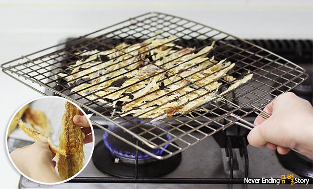 껍질을 벗겨 얇게 찢은 북어포를 석쇠에 놓고 약한 불에서 굽고 있는 모습이다.