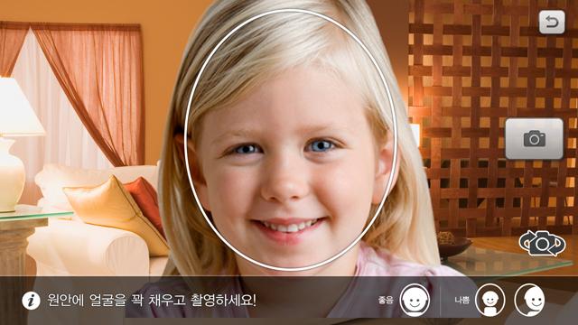 여자 아이가 자신의 얼굴사진을 찍어 애니메이션 동화에 넣을 아바타를 만들고 있다.