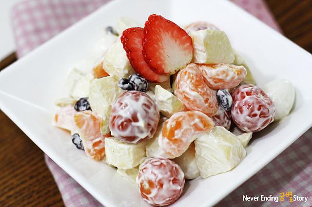 마요네즈와 설탕을 넣어 새콤달콤한 과일 샐러드로 귤, 방울토마토, 사과 등 각종 과일이 고루 들어가 있다.