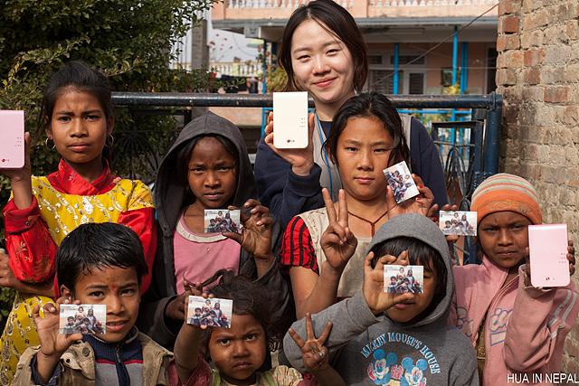 봉사단원과 네팔 학생들이 함께 찍은 단체사진. 모두 한 손에 포켓포토 혹은 포켓포토로 뽑은 사진을 들고 있다.