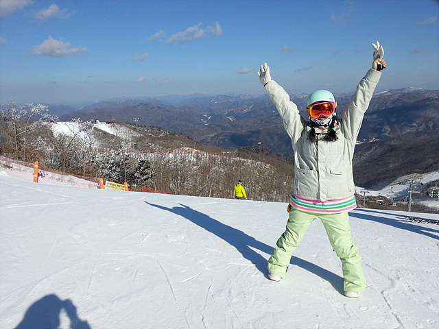 하이원 리조트 스키장 위에서 두 팔을 크게 벌려 포즈를 취하고 있다.