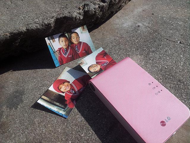 바닥에 포켓포토가 놓여 있고 그 주변에 포켓포토로 뽑은 네팔 학생들의 사진 3장이 놓여 있다.